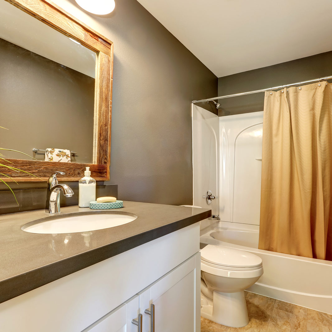 Interior of bathroom . Grey walls with white bathroom appliances. Has full bath shower with beige curtain toilet and vanity cabinet. Northwest USA