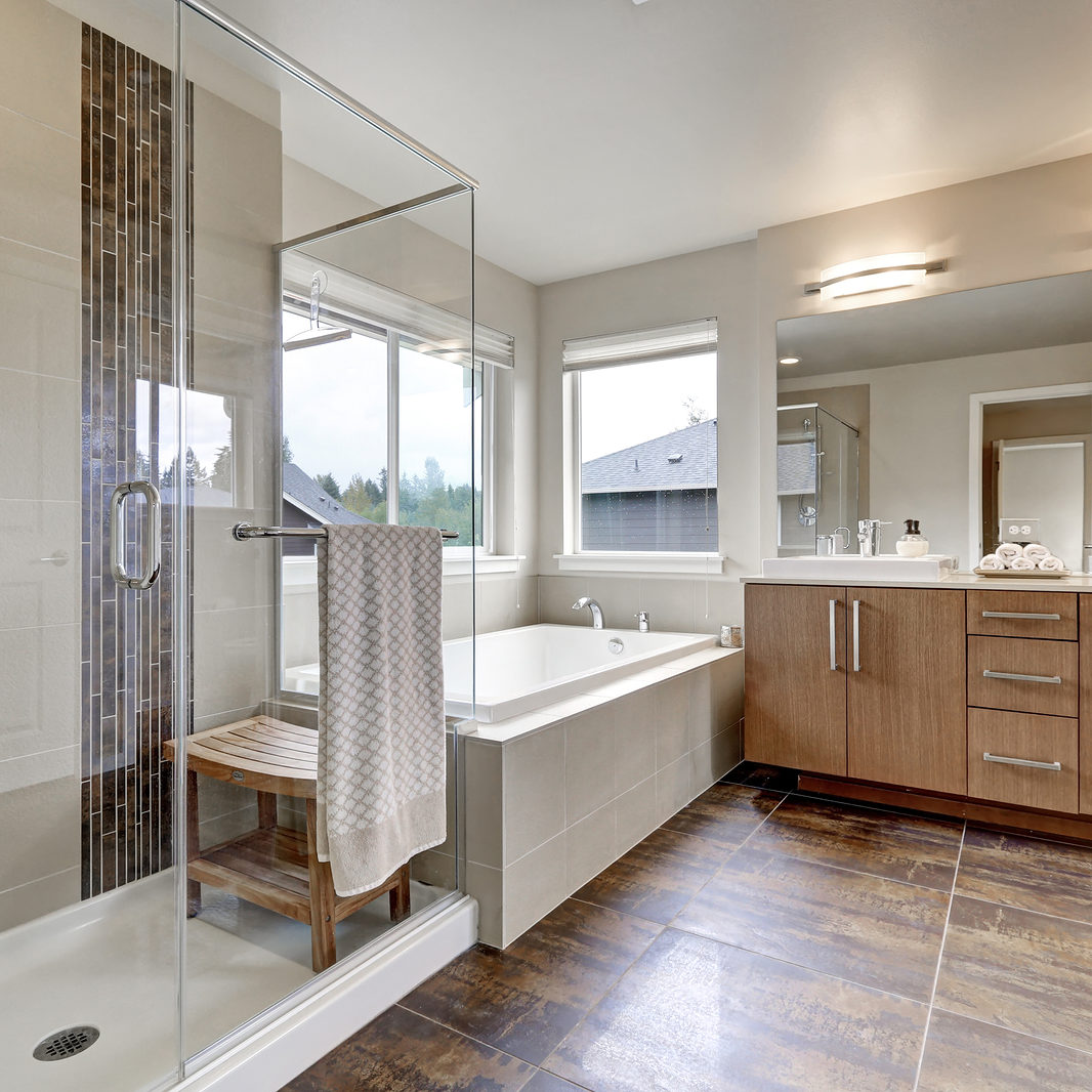 White modern bathroom interior in brand-new house. Double sink vanity with large mirror walk-in shower white bath tub and brown tile floor. Northwest USA
